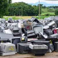 Television sets are piled up at a temporary storage site for earthquake debris in the city of Kumamoto's Higashi Ward Sunday. | KYODO