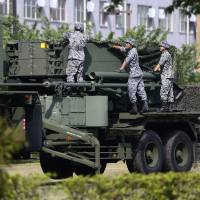 Self-Defense Forces members set up a PAC-3 Patriot missile unit deployed in case of a North Korean rocket launch at the Defense Ministry in Tokyo Tuesday. | AP