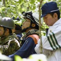 Police, fire station and Self-Defense Forces elements search for a missing boy in a Hokkaido forest Thursday. | KYODO