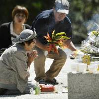 A woman prays Thursday for the victims of the Battle of Okinawa at the Peace Memorial Park in Itoman, where the final stage of the battle took place 71 years ago. | KYODO