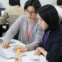 A teacher at Tech Camp, which offers intensive programming lessons, shows a student how to write computer code in Shibuya Ward, Tokyo, last September.   COURTESY OF TECH CAMP
