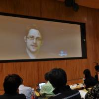 Edward Snowden, a former U.S. National Security Agency contractor who leaked secrets about the country's spying operations, speaks about U.S. surveillance activities in Japan via a video conference from Russia during a symposium in Tokyo on Saturday. | SHUSUKE MURAI