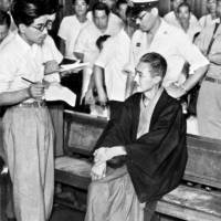 Sadamichi Hirasawa, who was convicted of fatally poisoning 12 people, answers questions from reporters at the Tokyo High Court on Aug. 11, 1951. | KYODO