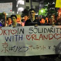 People at a candlelight vigil Tuesday evening in Tokyo's Shinjuku Ni-chome district show their solidarity with people in Orlando, Florida, where a gunman killed scores at a gay nightclub Sunday. | YOSHIAKI MIURA