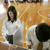 High school students practice voting on June 15 in Hino, Shiga Prefecture, which will hold a mayoral election on July 3. | KYODO