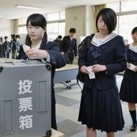 High school students in the city of Fukuoka take part in mock voting March 5 after hearing a debate by expected candidates for the Upper House election in July. | KYODO