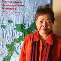 Peace campaigner Suzuyo Takazato stands in front of a map charting U.S. military sexual violence on Okinawa. | JON MITCHELL