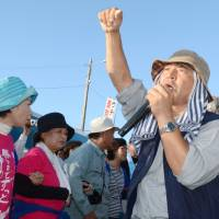 Hiroji Yamashiro speaks to protesters in front of the gates of U.S. Marine Corps Camp Schwab, Nago, in November 2015. | KYODO