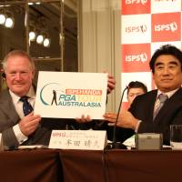 International Sports Promotion Society Chairman Haruhisa Handa (right) and PGA of Australia CEO Brian Thornburn hold up the logo of the ISPS Handa PGA Tour of Australasia at a news conference in Tokyo on June 6. | ISPS