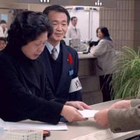 Japanese again: Hitomi Soga, who was abducted to North Korea in 1978, hands papers to an official at Mano town office on the island of Sadogashima, Niigata Prefecture, in 2002, to have her information reentered in her family's koseki family register. Soga had been removed from the family register as a missing person 16 years earlier. | KYODO