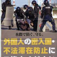 Keen on the rough stuff: A poster put up by the Ibaraki police in 2007 show the prefecture's boys in blue tackling assumed illegal foreign invaders.