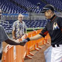 Warren Cromartie shakes hands with Ichiro before a Marlins game against the Nationals on May 22, in Miami. | KYODO