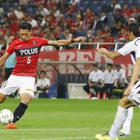 Urawa's Tomoaki Makino scores a 72nd-minute equalizer against FC Tokyo on Wednesday night. Reds went on to win the match 3-2. | KYODO