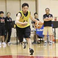 Guard Yuta Tabuse dribbles as head coach Kenji Hasegawa (far right) looks on during Wednesday's training camp for the provisional Japan men's national team at the National Training Center in Tokyo. | KAZ NAGATSUKA