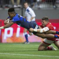 Japan holds on after red card to beat Canada
