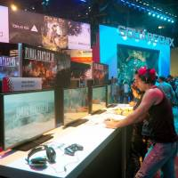 Visitors play 'Final Fantasy XV' on the opening day of the Electronics Entertainment Expo, one of the biggest showcases for new video games, in Los Angeles on June 14. | KYODO