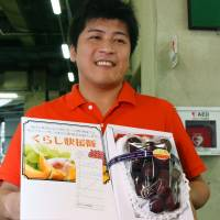 Takamaru Konishi, 37, a buyer for a supermarket in Hyogo Prefecture, submitted the winning bid for a batch of Ruby Roman grapes that went for a record ¥1.1 million at a wholesale market in Kanazawa, Ishikawa Prefecture, on Thursday. kyodo