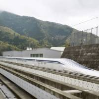 A magnetically levitating train operated by Central Japan Railway Co. making a test run is seen on an experimental track in Tsuru, Yamanashi Prefecture, on April 21, 2015. | REUTERS/KYODO
