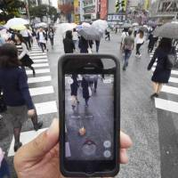 A phone screen shows a 'Pokemon Go' monster in Tokyo's Shibuya area on Friday. It has broken records as the fastest-downloaded smartphone game of all time. The delayed release in Japan was blamed on worries over server capacity. | KYODO