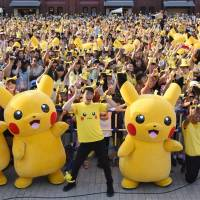 People dressed as Pikachu, a famous Pokemon character, dance with fans at the finale of the nine-day 'Pikachu Outbreak' event in Yokohama last August. | AFP-JIJI