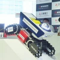 A Mitsubishi Heavy Industry Ltd. worker demonstrates Sakura No. 2, a spark-free robot suitable for use at disaster sites where explosive gases may be present. The display took place Tuesday at the company's office in Tokyo's Minato Ward. | SHUSUKE MURAI