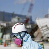 A Tokyo Electric employee in protective gear walks in front of the No. 1 reactor building at the Fukushima No. 1 nuclear power plant in the town of Okuma, Fukushima Prefecture, on Feb. 10.   BLOOMBERG
