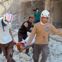 Civil defense members carry an injured man amid rubble of damaged buildings after an airstrike on Aleppo's rebel held al-Fardous district, Syria, Saturday.   REUTERS