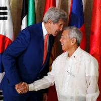 U.S. Secretary of State John Kerry whispers to Philippine Foreign Affairs Secretary Perfecto Yasay Jr. as they meet at the Department of Foreign Affairs in Pasay City, Metro Manila, Philippines, on Wednesday.   REUTERS