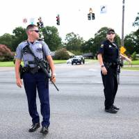 Police officers block off a road near the site of a shooting of police in Baton Rouge, Louisiana, Sunday. | REUTERS