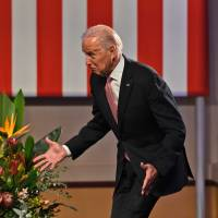 U.S. Vice President Joe Biden stumbles while walking onto the stage to deliver a speech at the Paddington Town Hall in Sydney on Wednesday.   AFP-JIJI