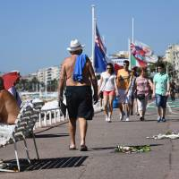 People walk Sunday on the Promenade des Anglais next to flowers left as a tribute to victims of the Bastille day deadly attack in Nice, France. Tunisian attacker Mohamed Lahouaiej-Bouhlel visited the Nice promenade with his rented truck on the two days before he rammed the vehicle into a crowd, killing 84, a source close to the investigation said Sunday.   AFP-JIJI