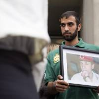 Nadeem Jeries holds a photo of Sammy Yatim, who he says was his best friend in high school, at a Toronto courthouse after the sentencing of Constable James Forcillo in Toronto on Thursday. Forcillo, a Toronto police officer, was sentenced to six years in the shooting death of Yatim in a case that sparked protests in Canada's largest city after it was caught on video and posted on YouTube.   MICHELLE SIU / THE CANADIAN PRESS VIA AP
