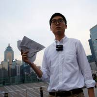 Pro-independence Hong Kong National Party convenor Chan Ho-tin holds a form saying the city is an 'inalienable' part of China, which he has torn into pieces, after being disqualified from running in Legislative Council elections on Saturday. | REUTERS