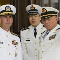 Commander of the Chinese Navy Adm. Wu Shengli (right) points out the layout of the Chinese Navy Headquarters to visiting U.S. Chief of Naval Operations Adm. John Richardson (left,)in Beijing, Monday. Richardson met Wu during his trip to Beijing and the port city of Qingdao that began on Sunday. He is also scheduled to visit the navy's submarine academy, tour China's first aircraft carrier and discuss ongoing Rim of the Pacific military drills. | AP