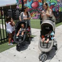 Two women walk Friday with their children in Miami's Wynwood neighborhood, where four people have become infected with the Zika virus. | AP