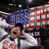 A California delegate reacts as a delegate from New York holds up a Donald Trump flag during the second day of the Republican National Convention in Cleveland on Tuesday.   AP
