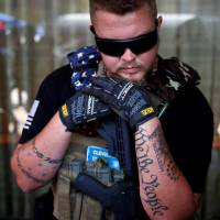 West Ohio Minutemen member Trevor Leis, whose tattoos include the words 'We the People' from the Constitution, rests on his assault rifle while taking a break from patrolling downtown Cleveland during the Republican National Convention on Tuesday.   REUTERS