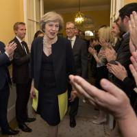 May takes U.K. helm, taps Johnson for top envoy, Hammond for finance