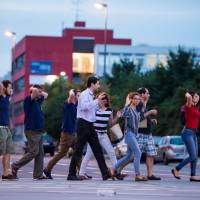 People walk with their hands up as they are evacuated from the Olympia shopping mall in Munich on Friday following a shooting that left at least 10 dead, including the gunman.   AFP-JIJI