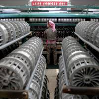 A woman works at the Kim Jong Suk textile mill in Pyongyang during a government-organized visit for foreign reporters in Pyongyang on May 9.   REUTERS