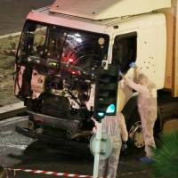 Investigators inspect a rental truck that a Tunisian-born man, 31, rammed into Bastille Day crowds in the French city of Nice on Thursday. Police shot the driver to death after he brought carnage along a 2-km stretch of the seafront. | AP