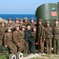 North Korean leader Kim Jong Un poses with soldiers during an inspection of an outpost on the Sea of Japan coast in this undated photo released July 7.   REUTERS