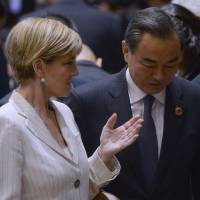 Australian Foreign Minister Julie Bishop talks with Chinese Foreign Minister Wang Yi during the East Asia Foreign Ministers' meeting on the sidelines of the Association of Southeast Asian Nations annual ministerial meeting in Vientiane on Tuesday. | AFP-JIJI