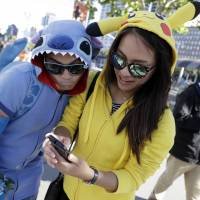 A woman dressed as the Pokemon character Pikachu (right) participates in a 'Pokemon Go' search with a man dressed as the Disney character Stitch on Wednesday in San Francisco. | AP
