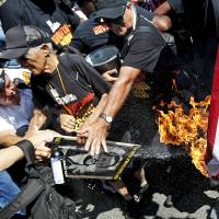 Flag-burning protesters arrested outside RNC as others build mock 'wall' against Trump