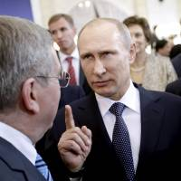 Russian President Vladimir Putin talks with International Olympic Committee President Thomas Bach in Sochi, Russia, in February 2014. | AP