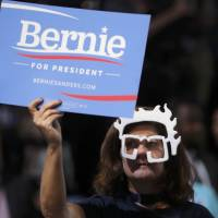 A supporter of former Democratic U.S. presidential candidate Bernie Sanders, wearing a Sanders mask, protests on the floor at the Democratic National Convention in Philadelphia Monday.   REUTERS