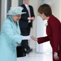 Queen Elizabeth II shakes hands with Scottish First Minister and Scottish National Party leader Nicola Sturgeon as she attends the opening of the fifth session of the Scottish Parliament in Edinburgh on Saturday. | AP