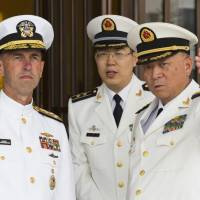 U.S. Chief of Naval Operations Adm. John Richardson (left) listens to Chinese Navy commander Adm. Wu Shengli (right) at Chinese Navy headquarters in Beijing on Monday. | AP