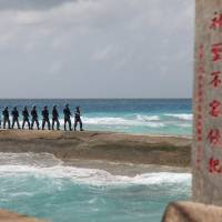 Chinese People's Liberation Army Navy personnel patrol in the Spratly Islands, known in China as the Nansha Islands, in February. The sign reads 'Nansha is our national land, sacred and inviolable.' | REUTERS